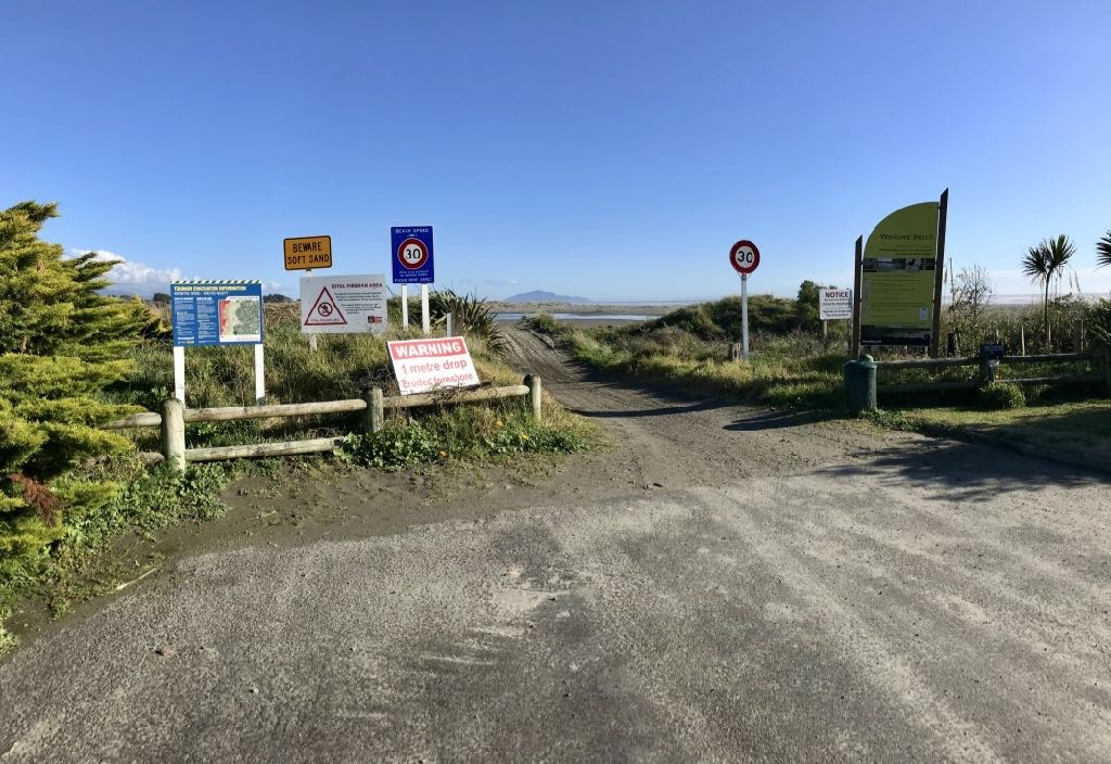 Too many signs at the vehicle entrance. Kāpiti Island in the background.