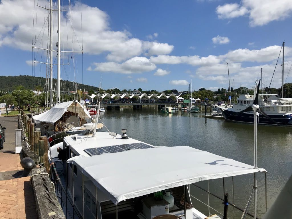 A view across a marina to market stalls.