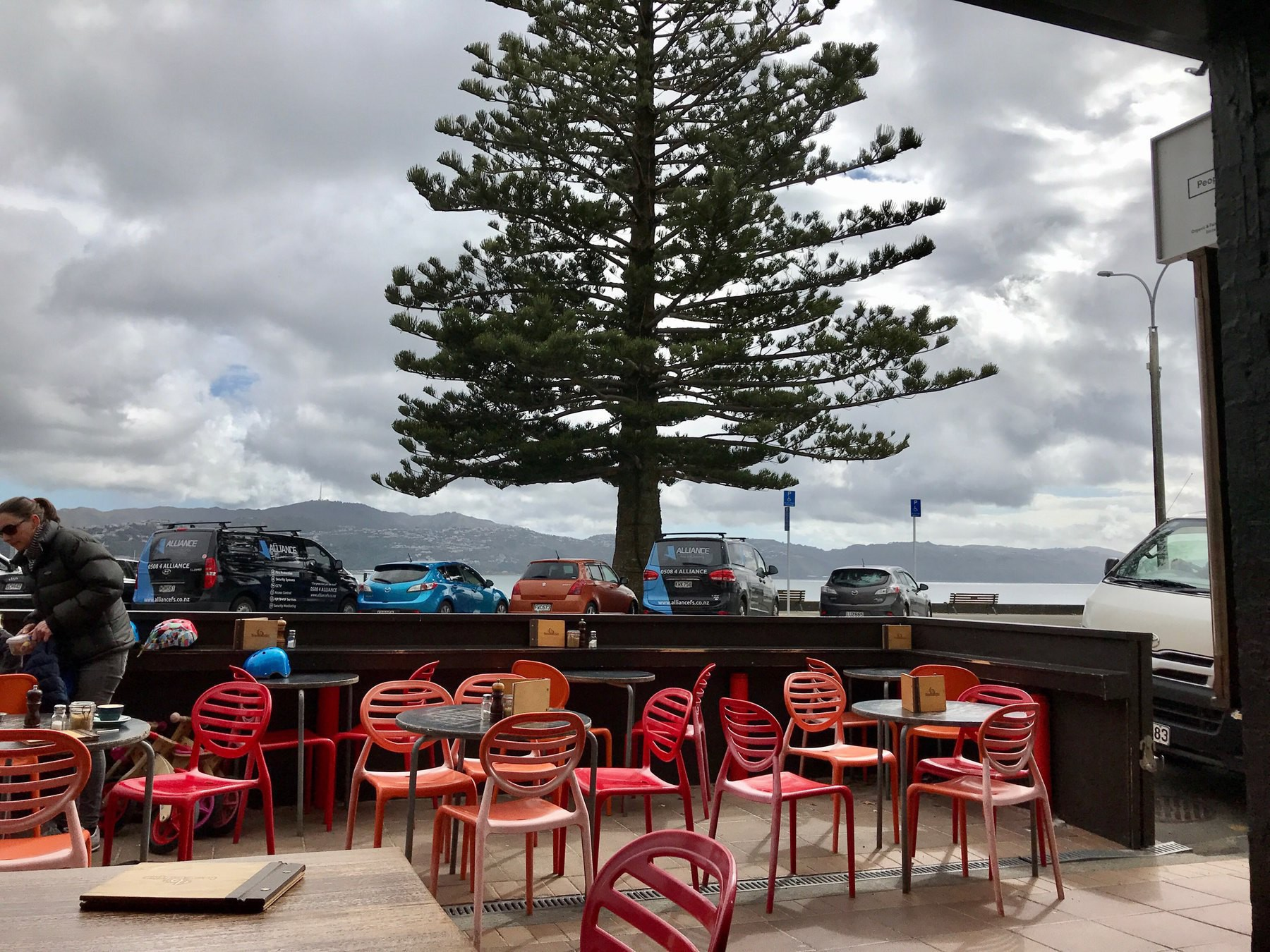 View across cafe tables and chairs to parked cars, with the harbour beyond.