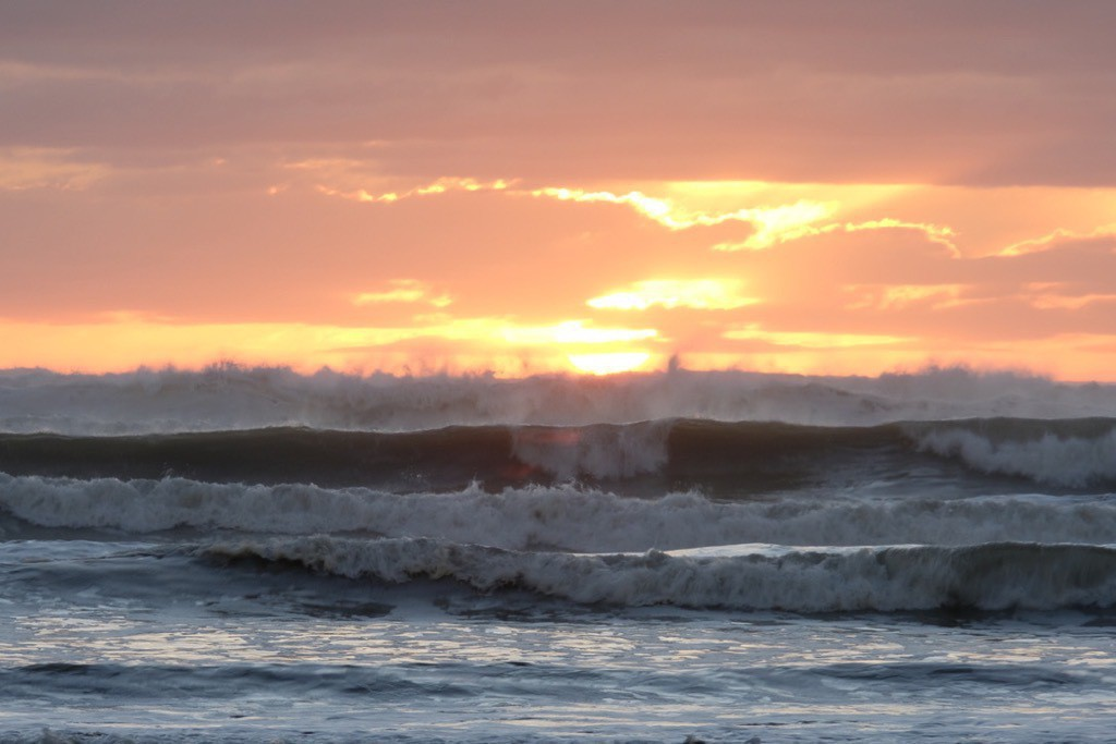 Big waves in the foreground, with orange sky.