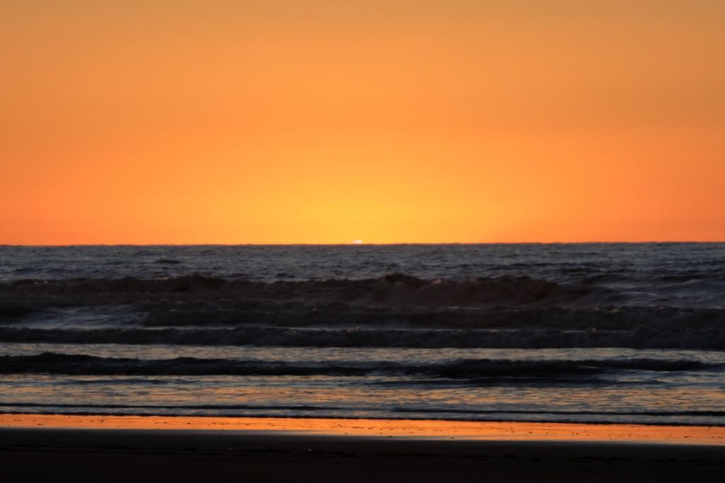 Across the sea. The sun is below the horizon with a hint of a 'flag' remaining.