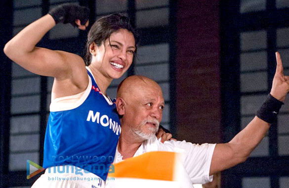 Still from the movie showing MaryKom and her coach with arms in the air celebrating a success.