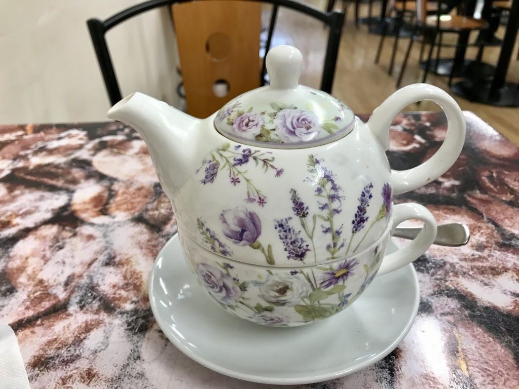 White teapot with painted flowers. The bottom half is actually the teacup.