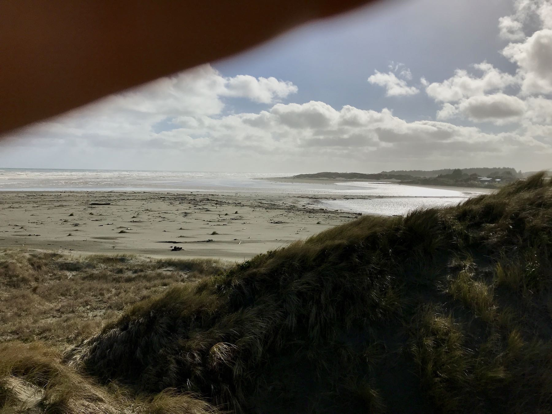 Photo of the river mouth, but with a hand obscuring top left, at an angle that mirrors a sand dune on the right.