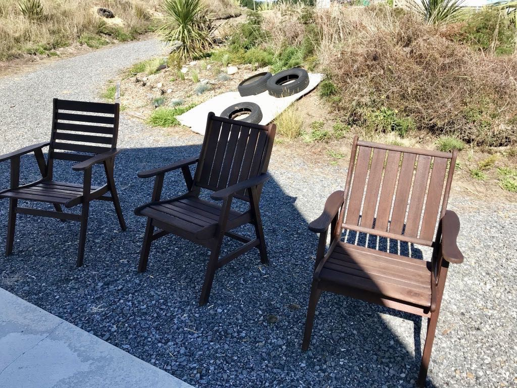 3 wooden outdoor chairs with a fresh coat of stain.