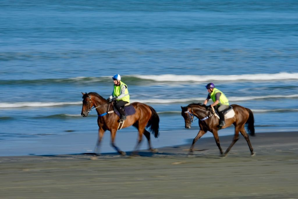 Two dark brown horses, with riders, on the beach. The horses legs are blurry.