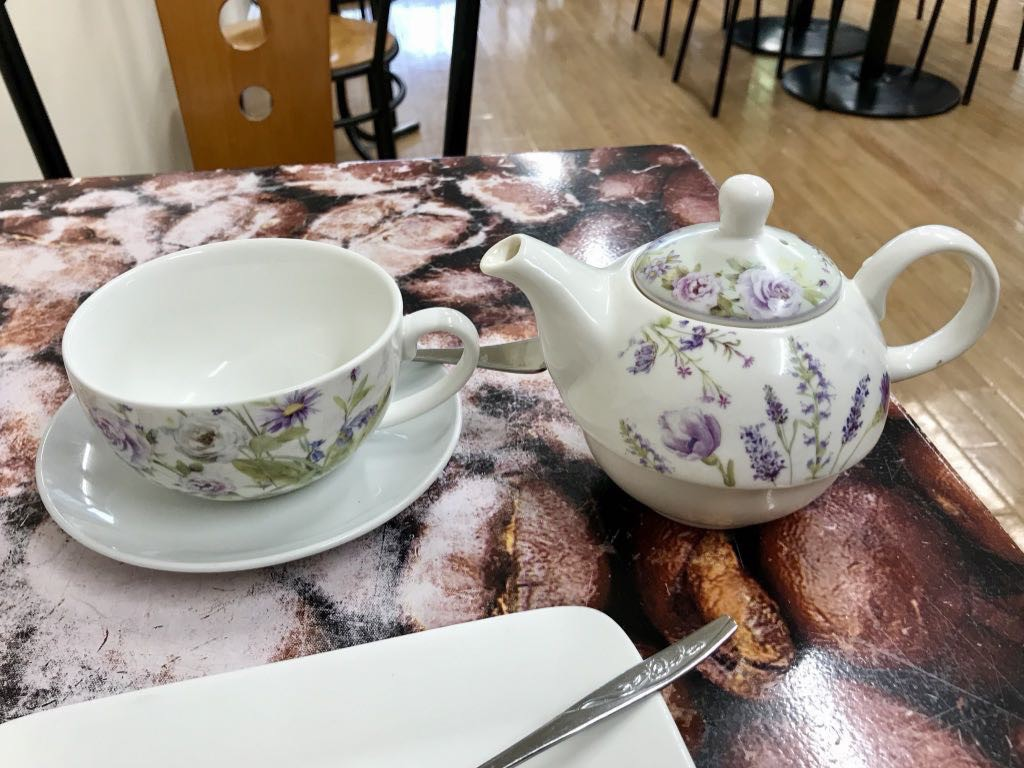 White teapot with painted flowers next to the teacup.