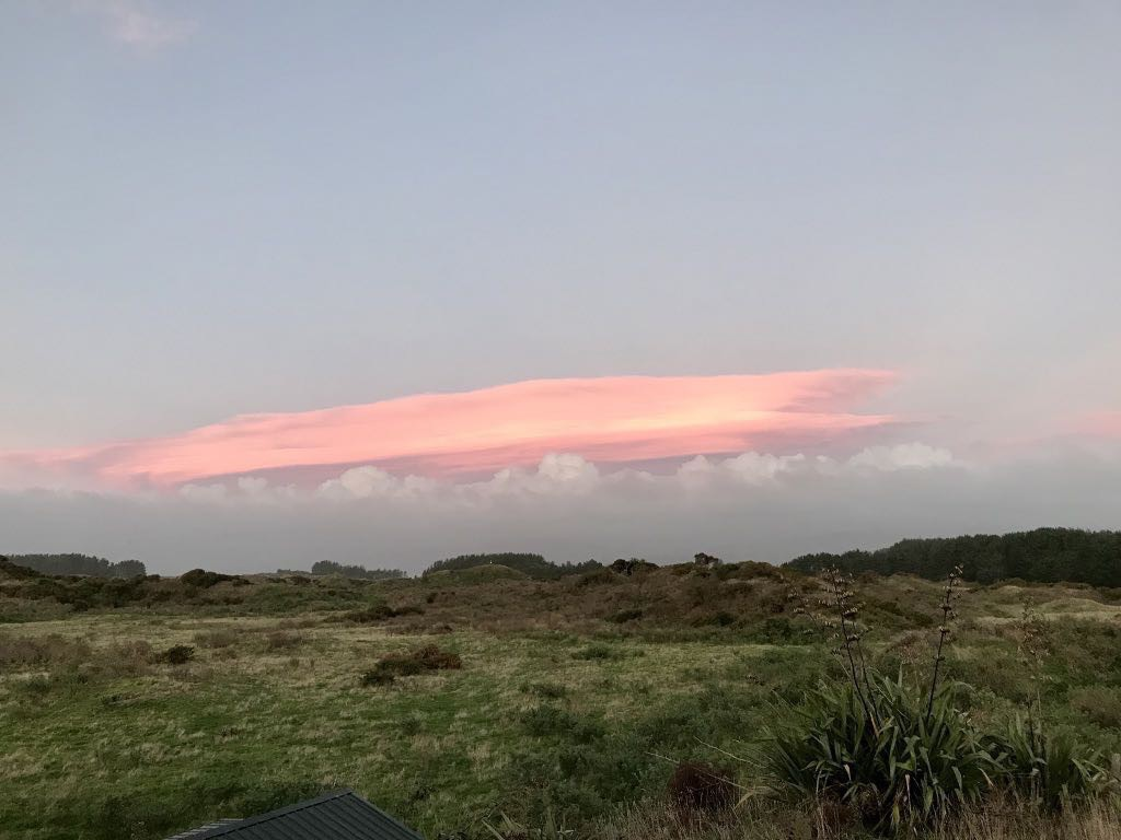 Very pink lenticular cloud. Above is blue sky. Below white cloud and sunlit paddocks.