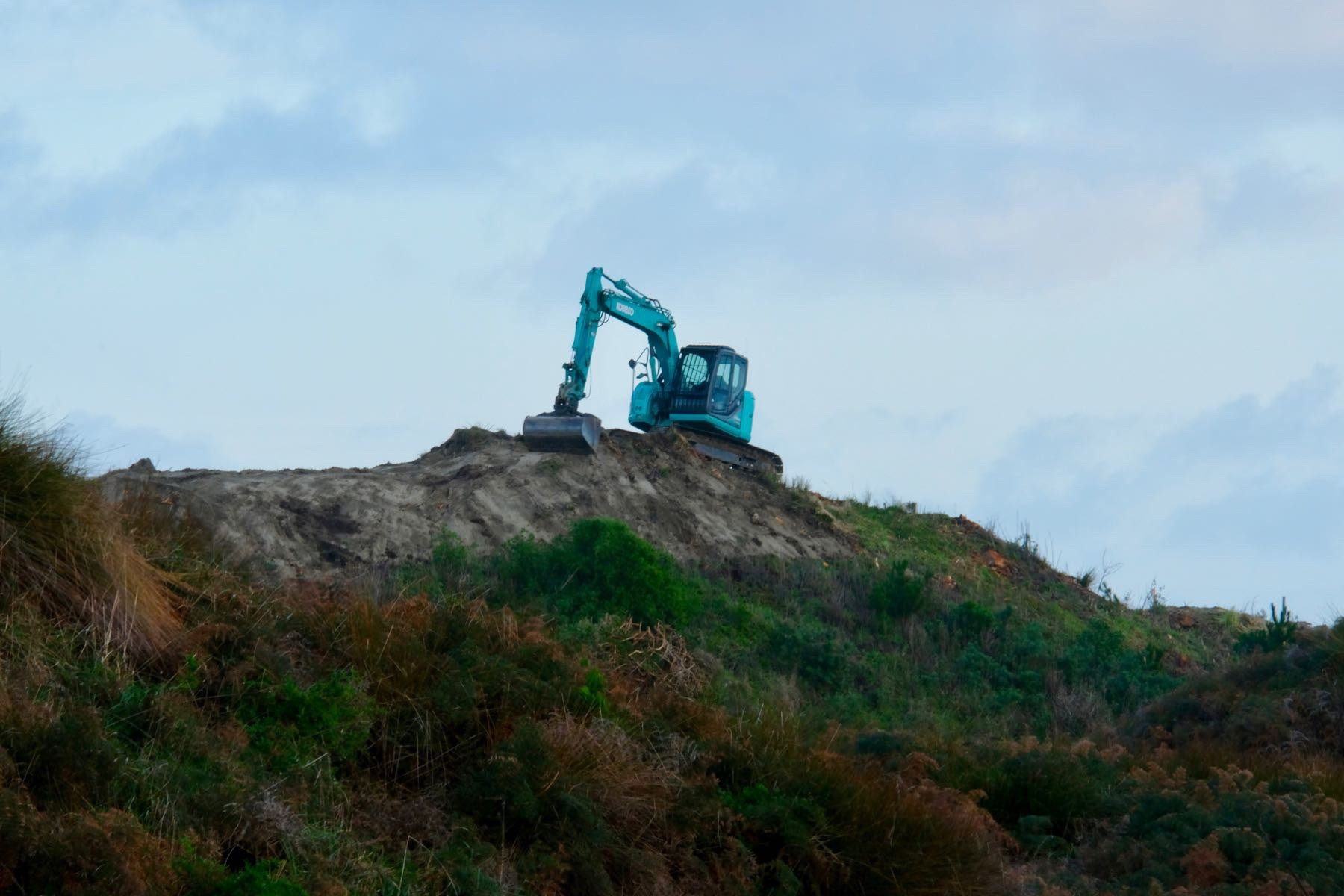 Digger removing the top of a hill it is sitting on.