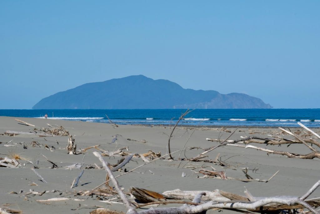 A view across the beach to Kāpiti Island. Blue sky and sunshine.
