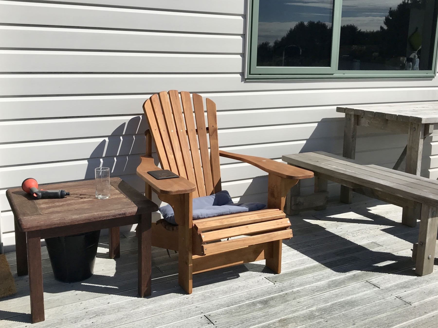 Adirondack style chair, with coffee table and Kindle.