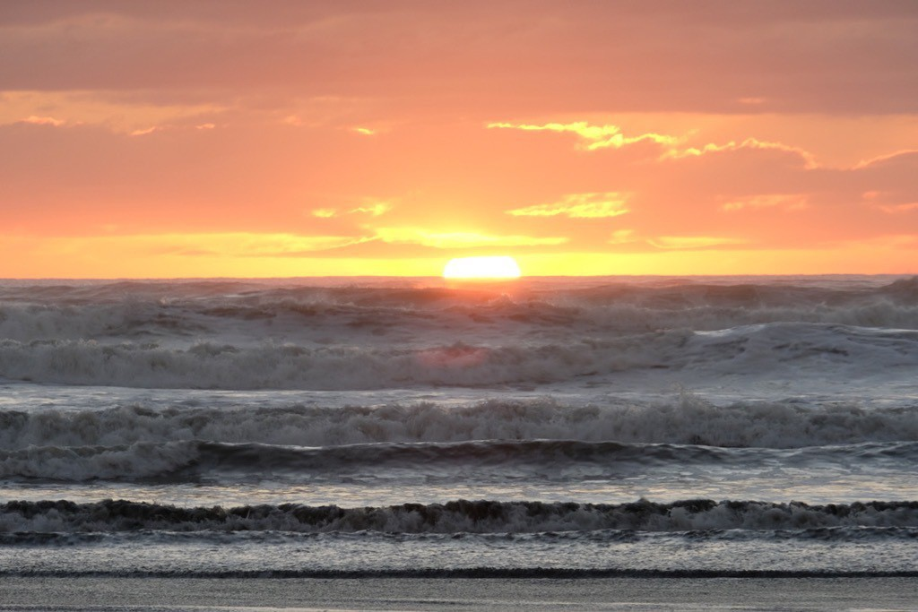 Orange sky with sun sinking below the horizon and waves like shelving in the foreground.