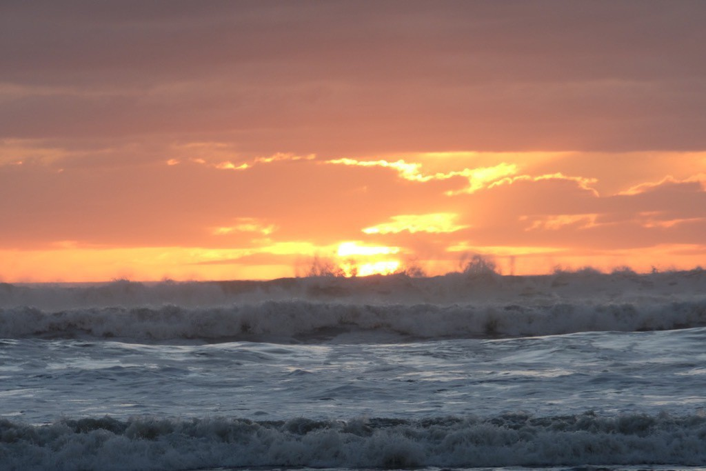Sea in foreground, dramatic orange sky, sea spray rising high on the horizon.