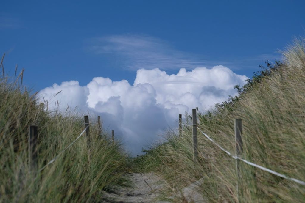 Beach track between dunes leading upwards with fluffy clouds in the V.