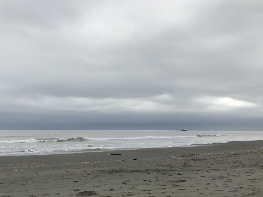 Pale grey sea, calm, with a fishing boat one one side.