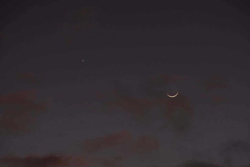 Dar sky with a hint of pink hue, Venus near top left and a tiny sliver of crescent moon on the right.