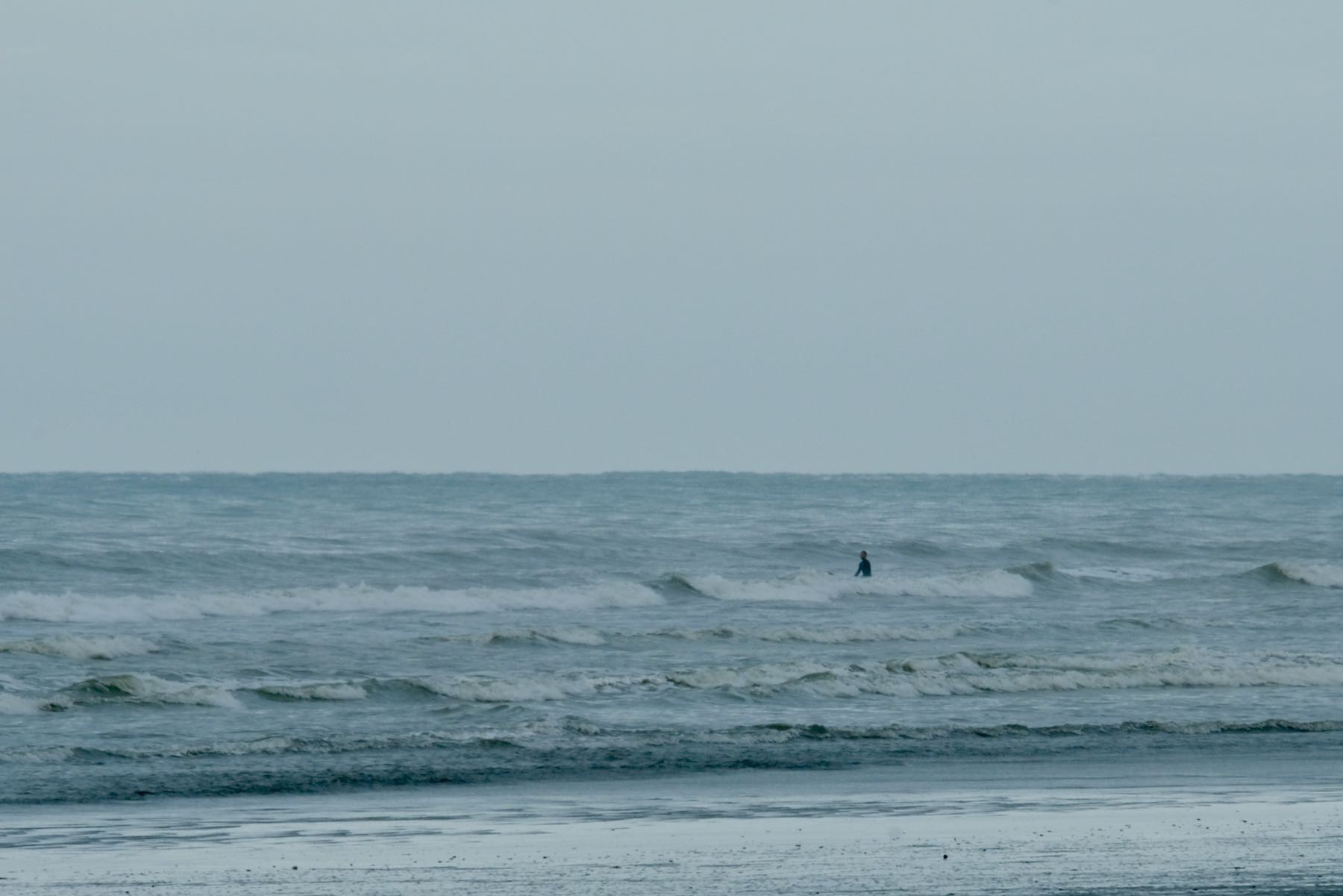 A person sitting on a surboard in the sea.
