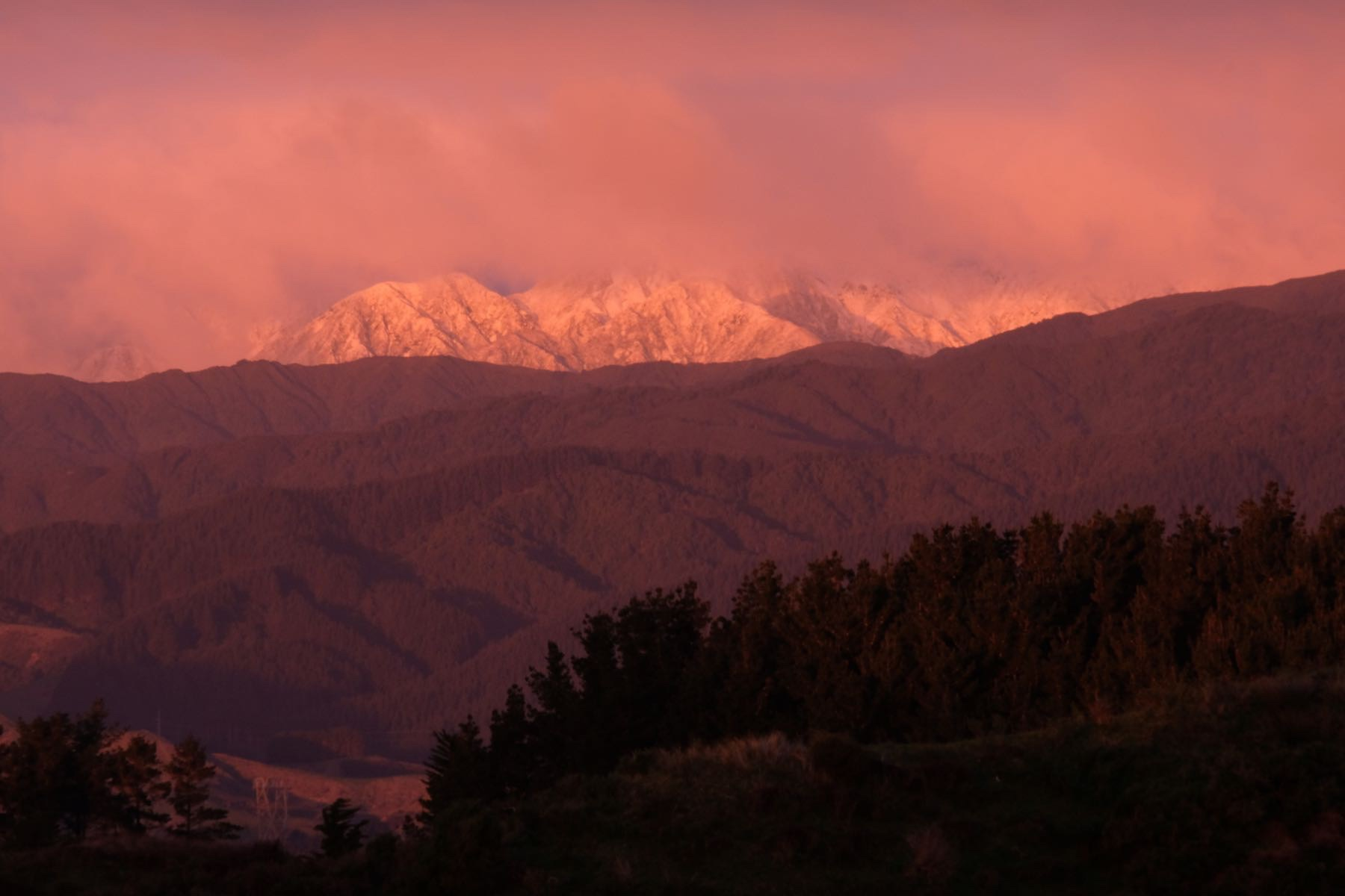 An orange sunset photo of a dusting of snow on the mountain peaks.
