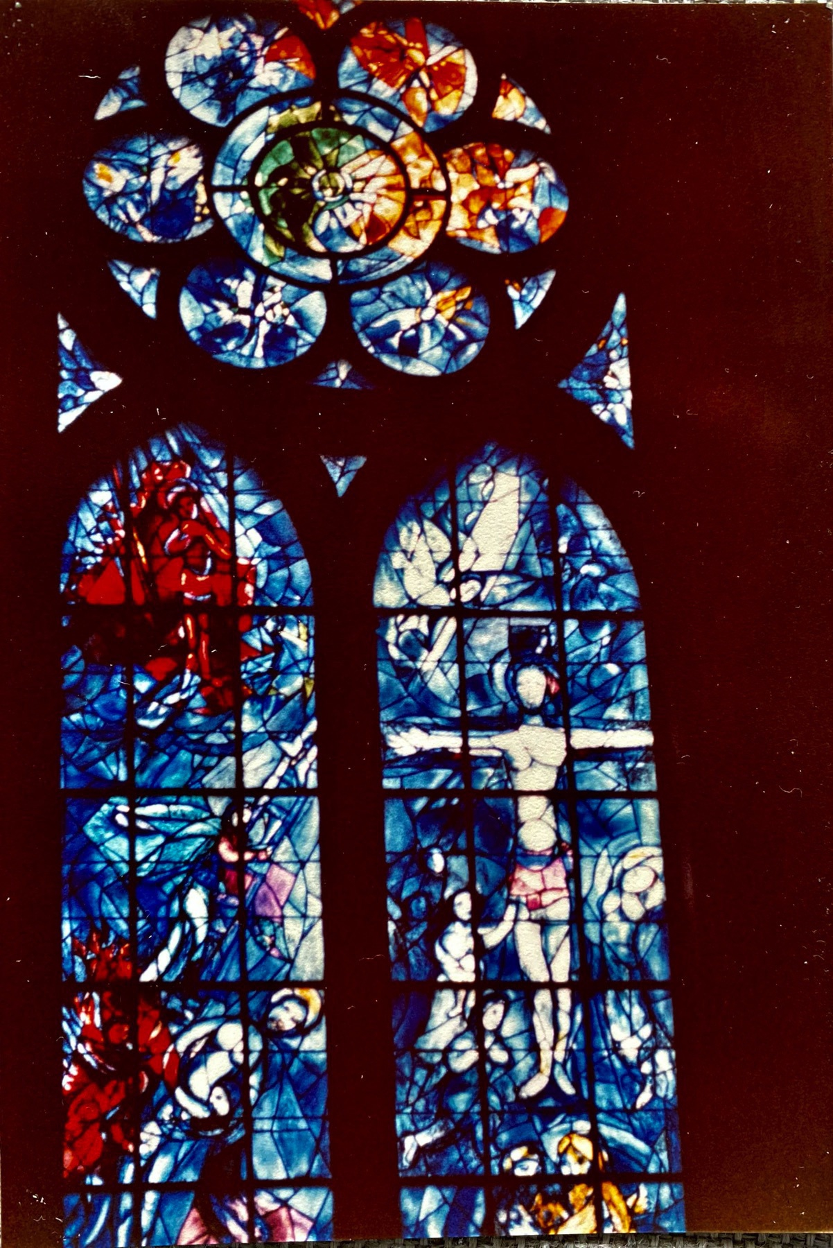 One cathedral window in stained glass with a predominant blue colour.
