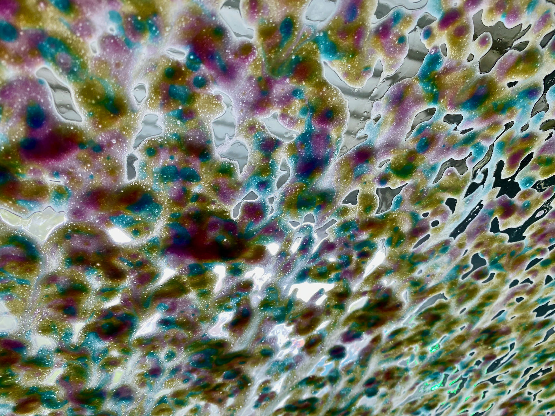 Multicoloured foam on the windcsreen, seen from inside the car.