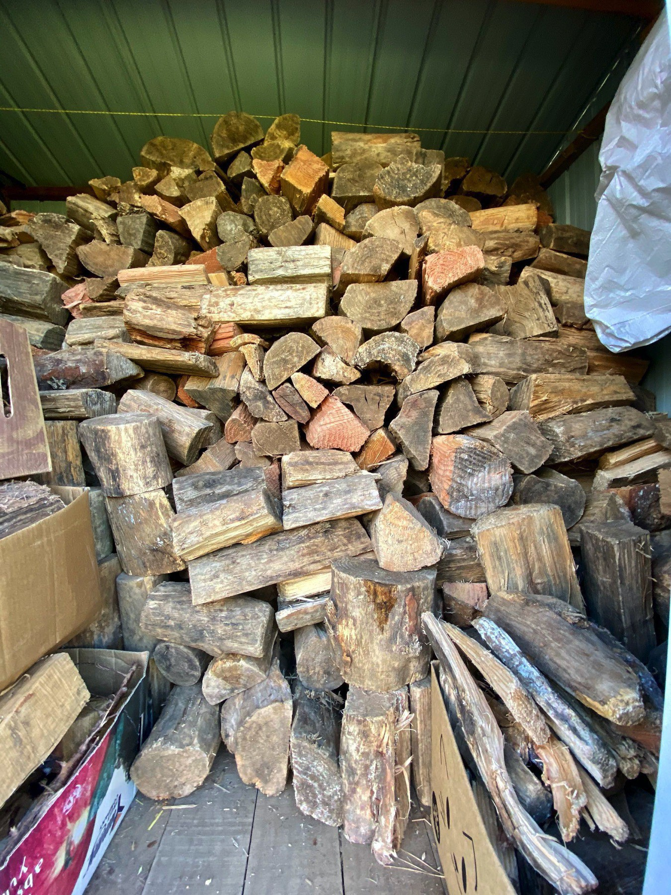 A load of stacked firewood in a shed.