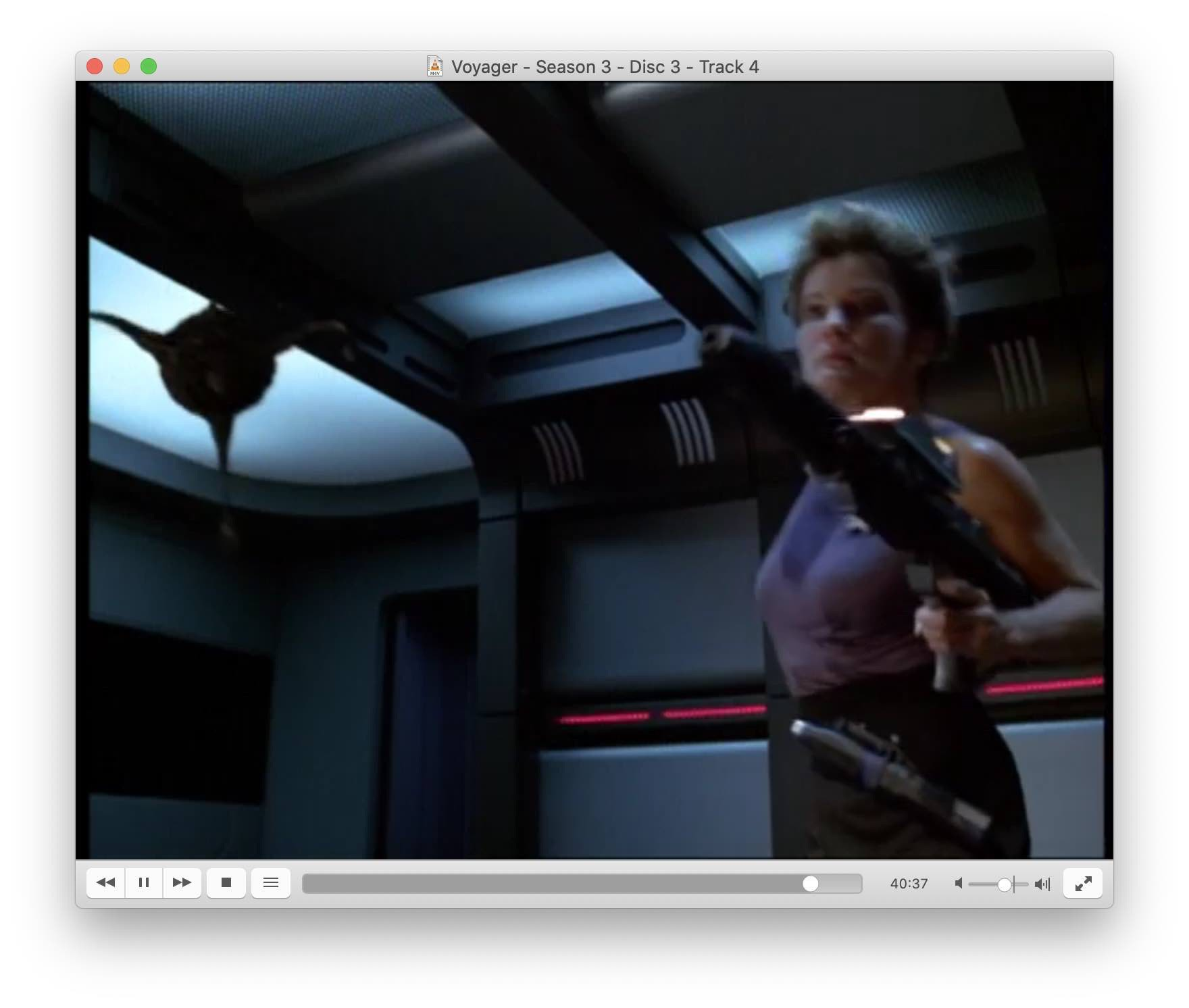 Screenshot from S3E11 showing Janeway with a big gun.
