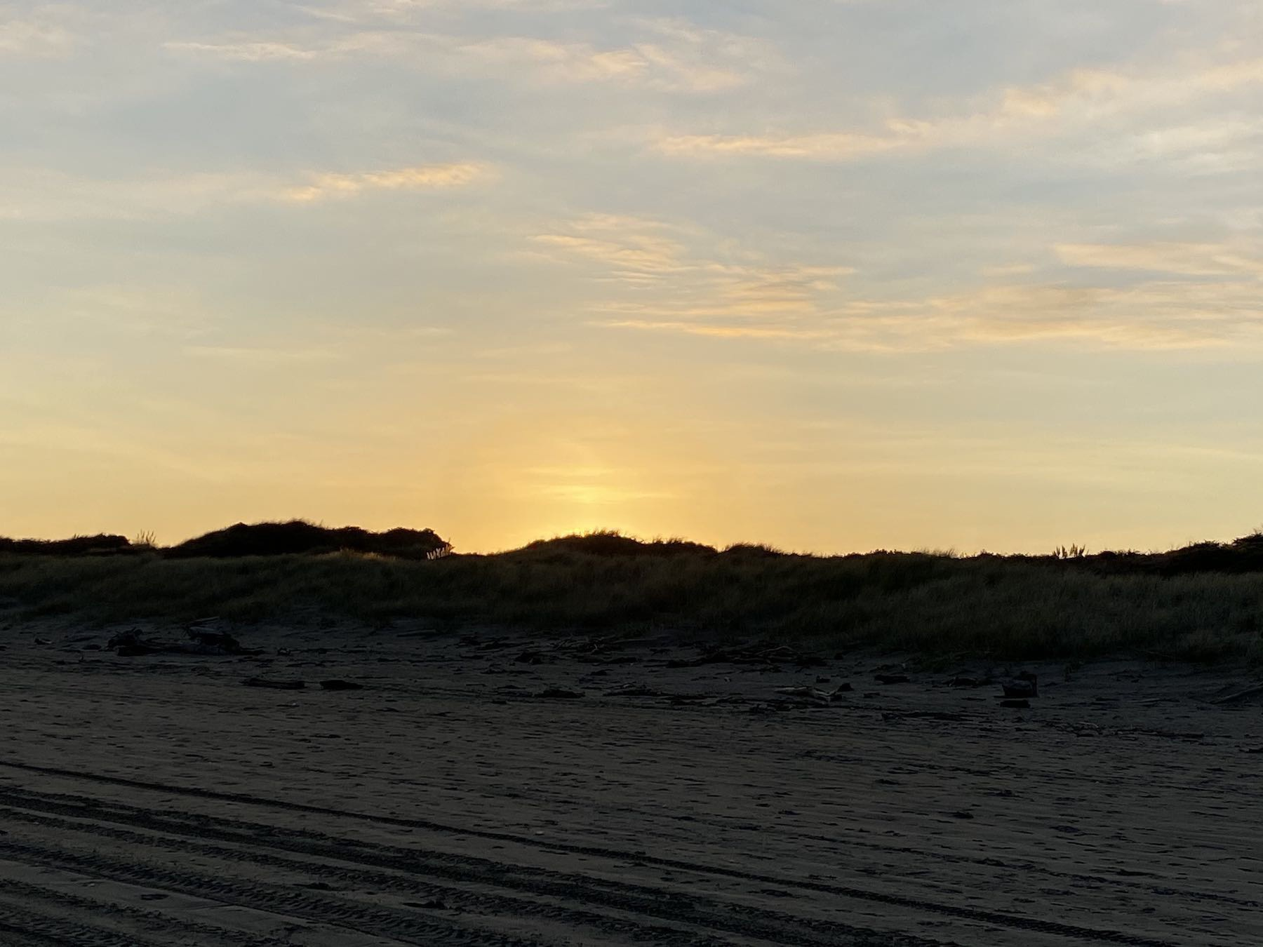 Sun rising behind a sand dune, with a halo of orange.
