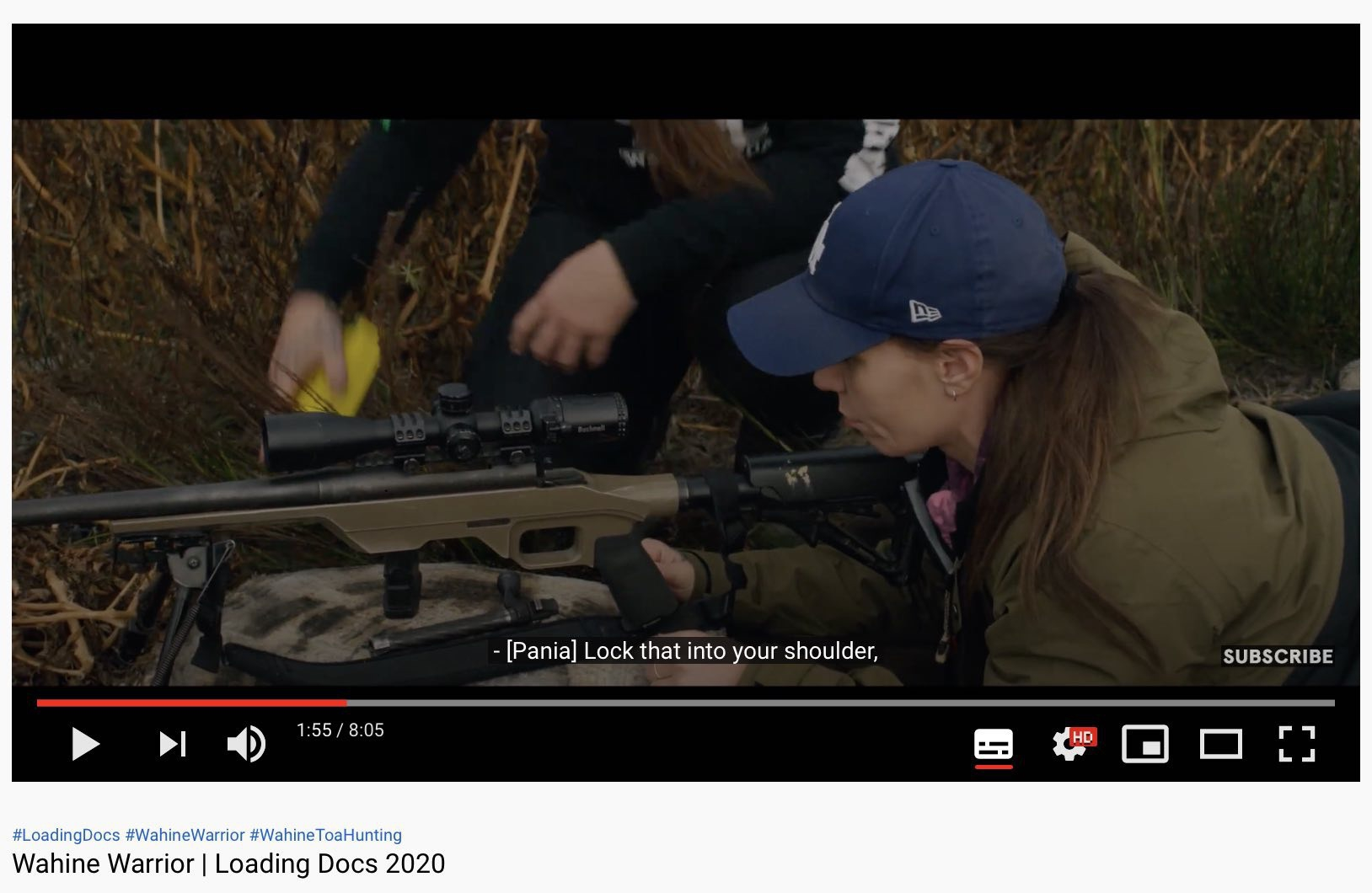 Still from the video showing a woman learning to use a hunting rifle.
