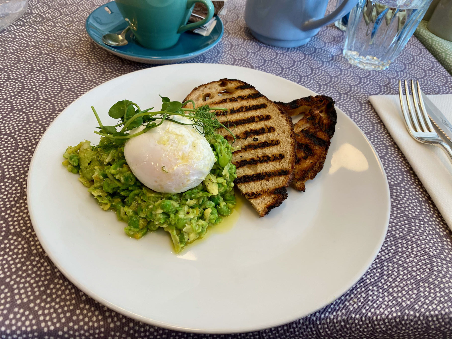Plate with Smashed peas & avocado, lemon, Parmesan, poached egg, toast.