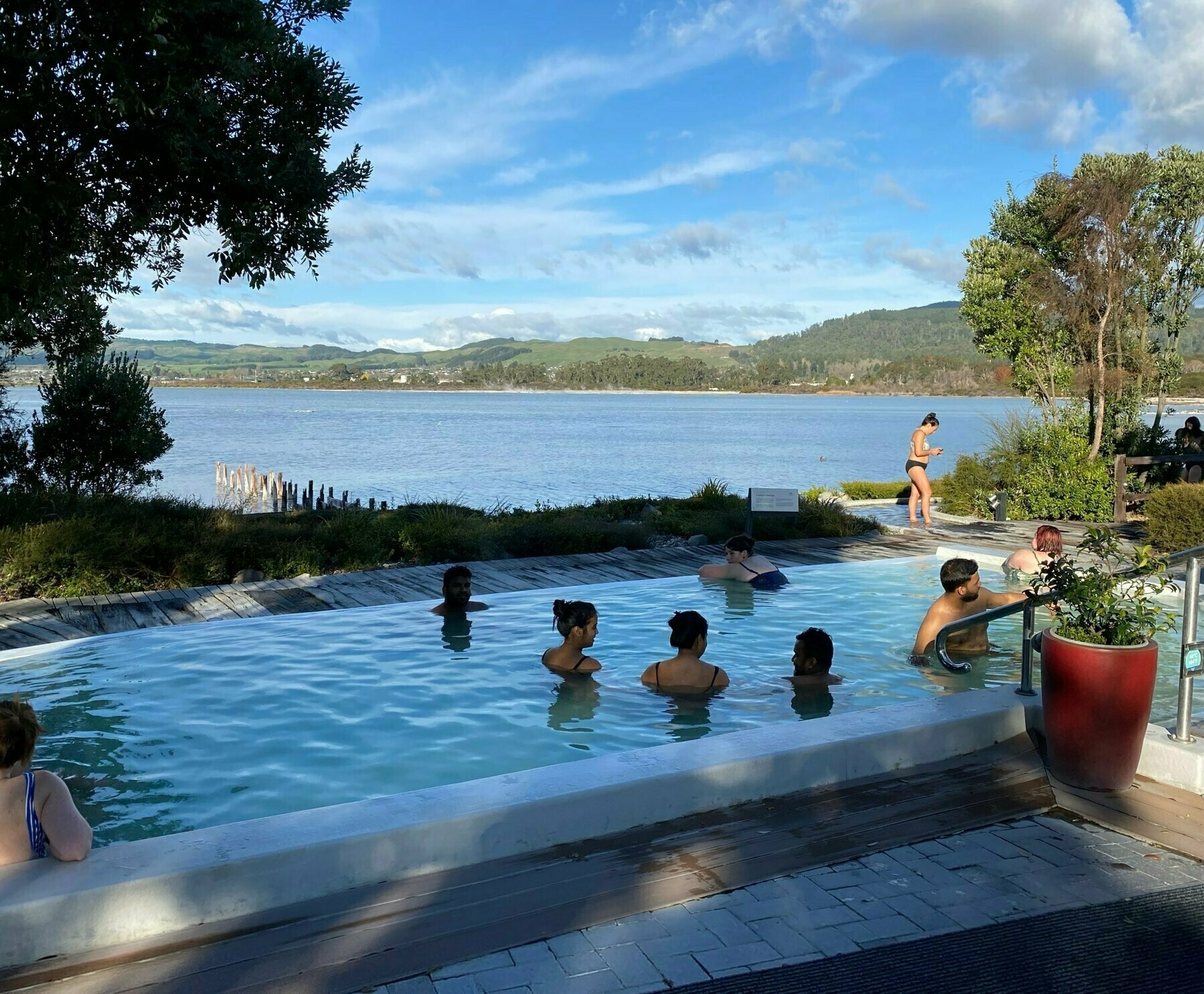 People in a thermal spa with Lake Rotorua behind.