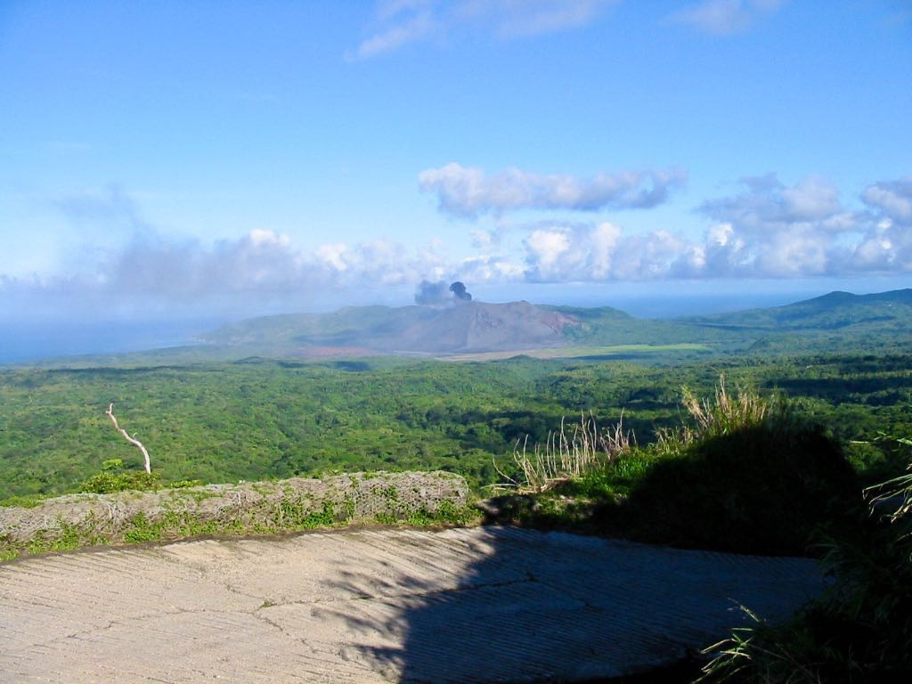 View across countryside to Mt Yasur which is belching smoke.