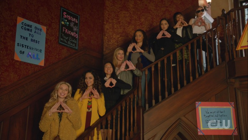Screenshot showing 8 women on a set of stairs, all flashing their sorority sign.