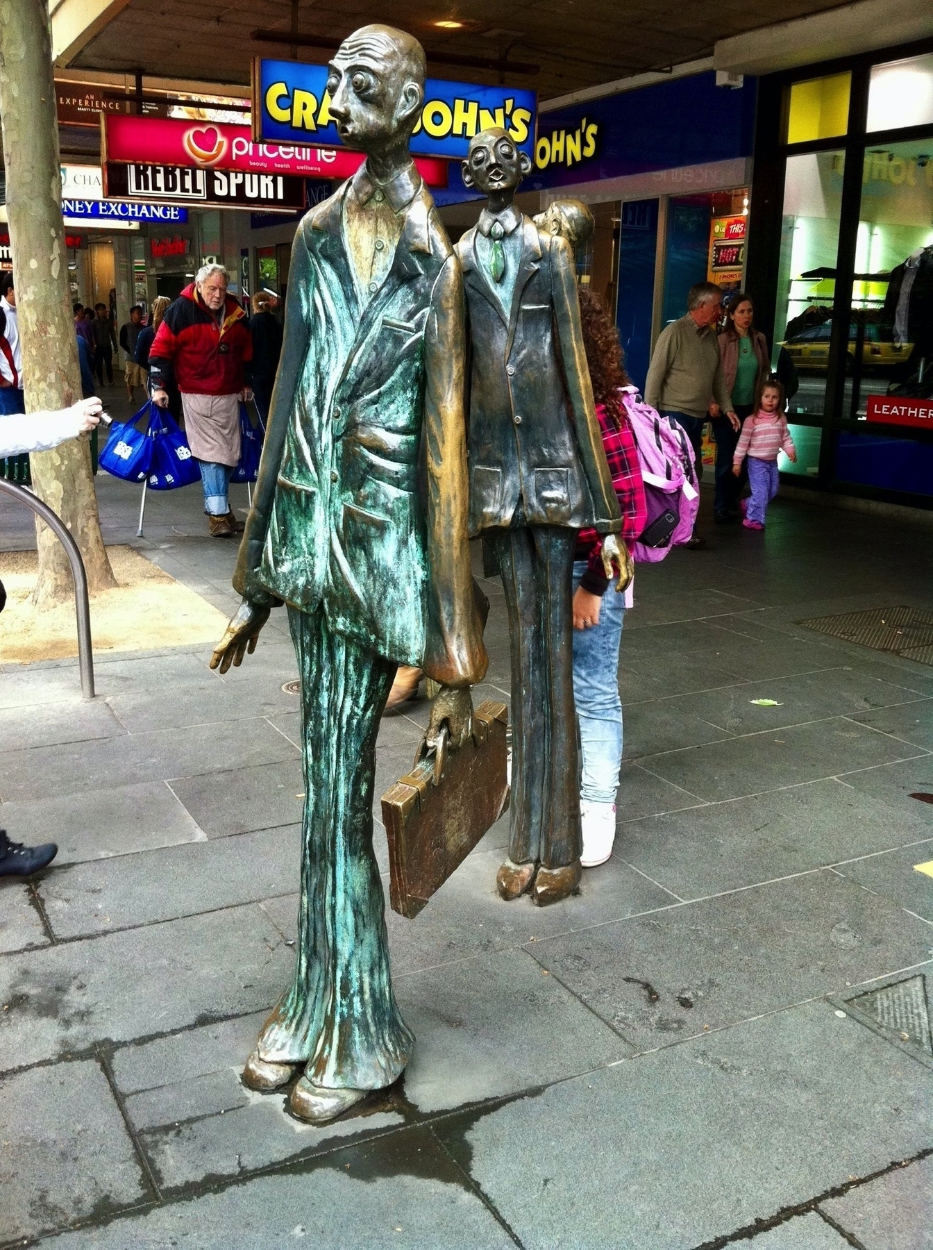 Life size statues of 3 skinny men. Another angle.