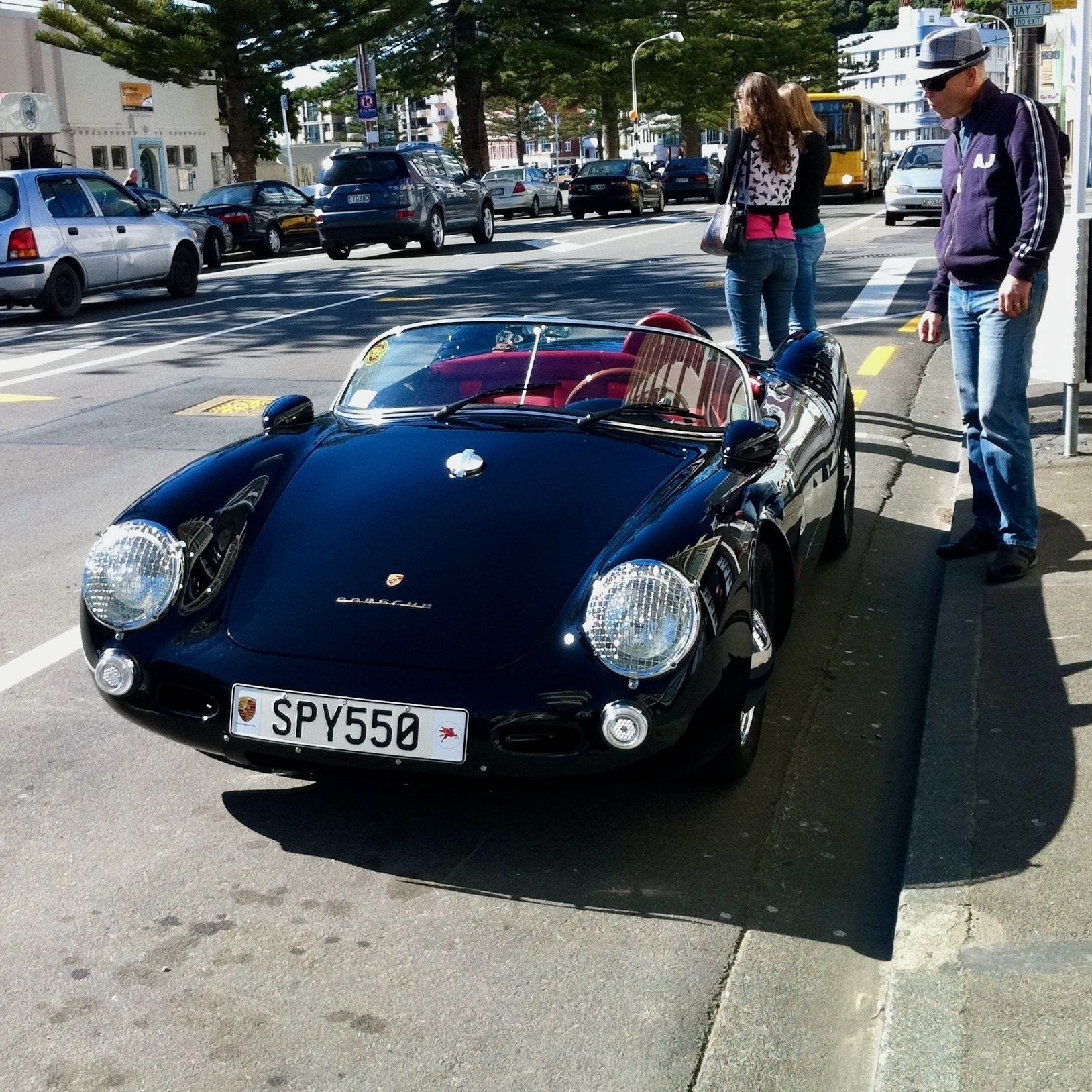 Porsche Spyder sports car front view, with a hipster admiring it.