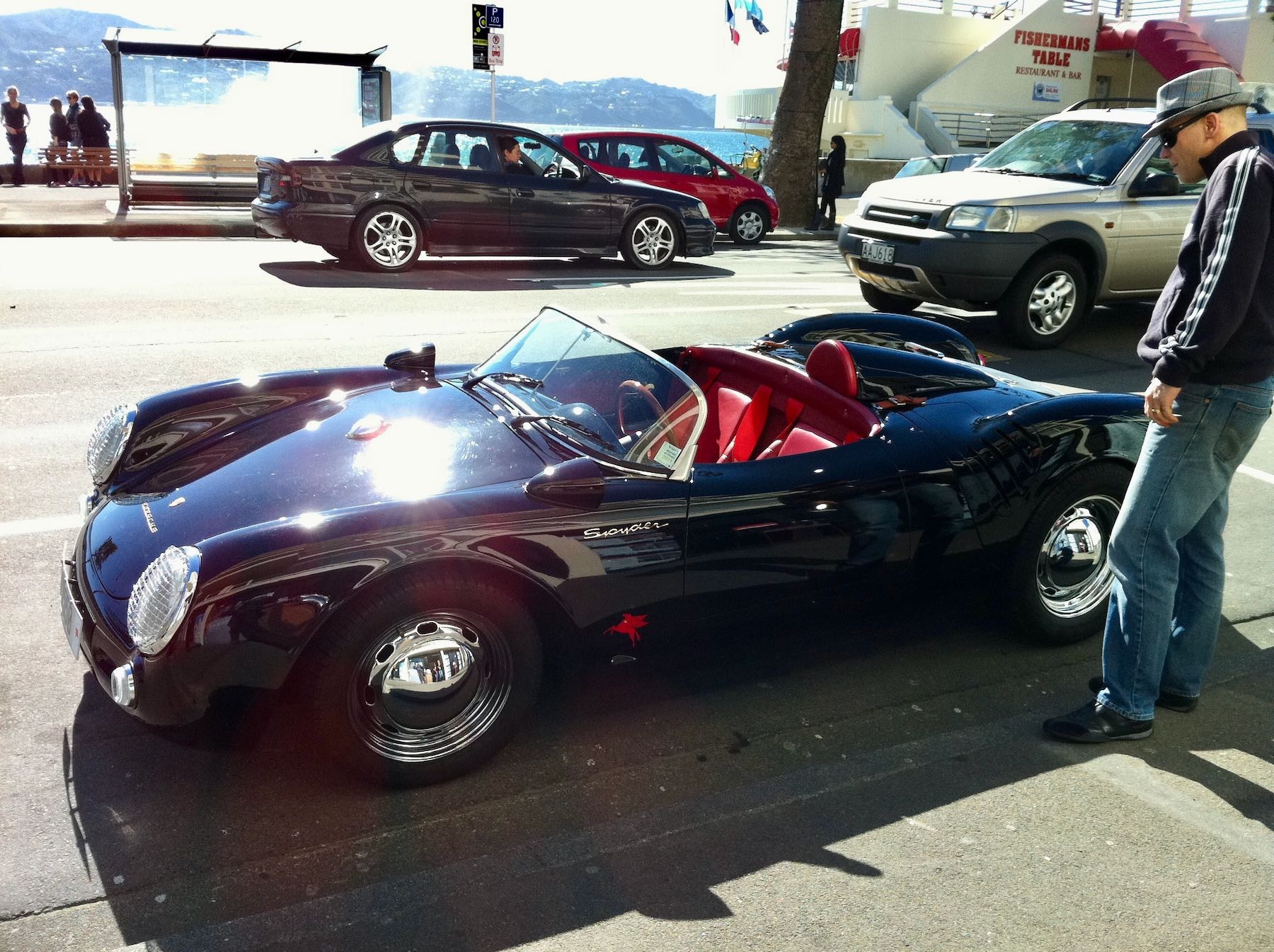 Porsche Spyder sports car, side view, with a hipster admiring it.