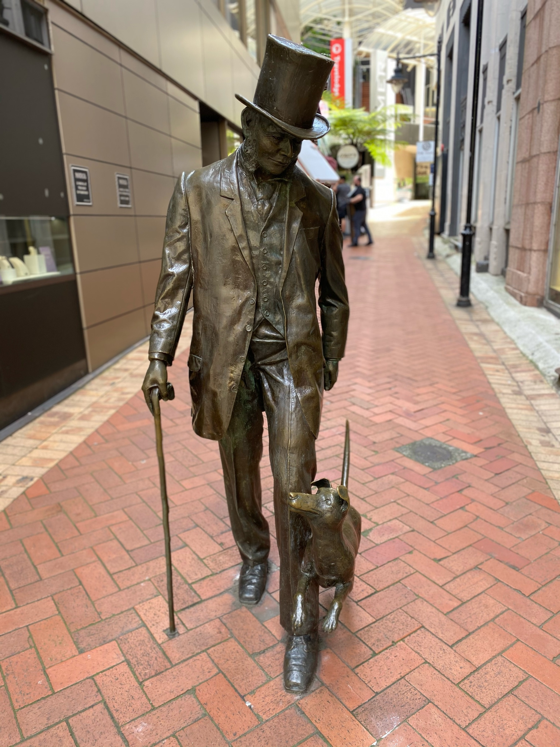 Statue of a man in a top hat with a small dog by his foot.