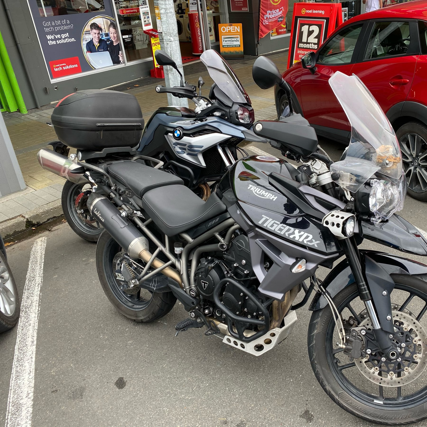 Two large motorcycles parked in a town.