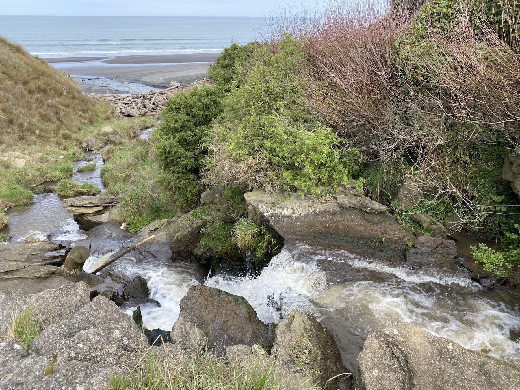 The lower waterfall, about 1 metre high, near beach level and flowing out to sea.