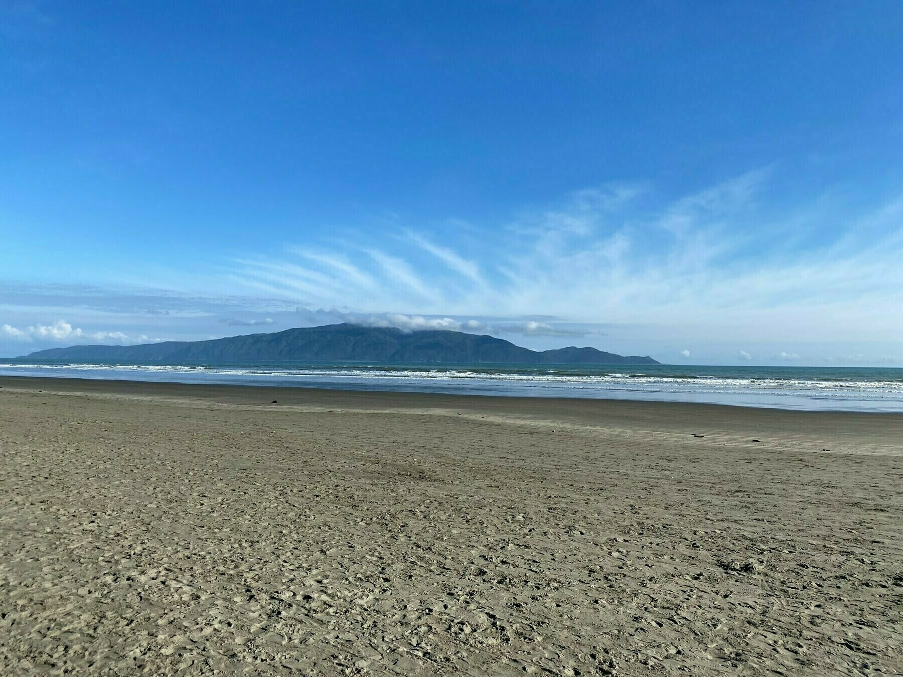 Looking across a beach and sea to a large island.