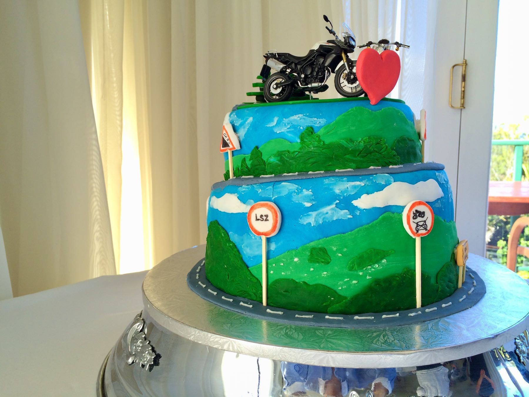 Two-layered wedding cake in blues and greens with a road winding up a hill, road signs and two bikes on top.