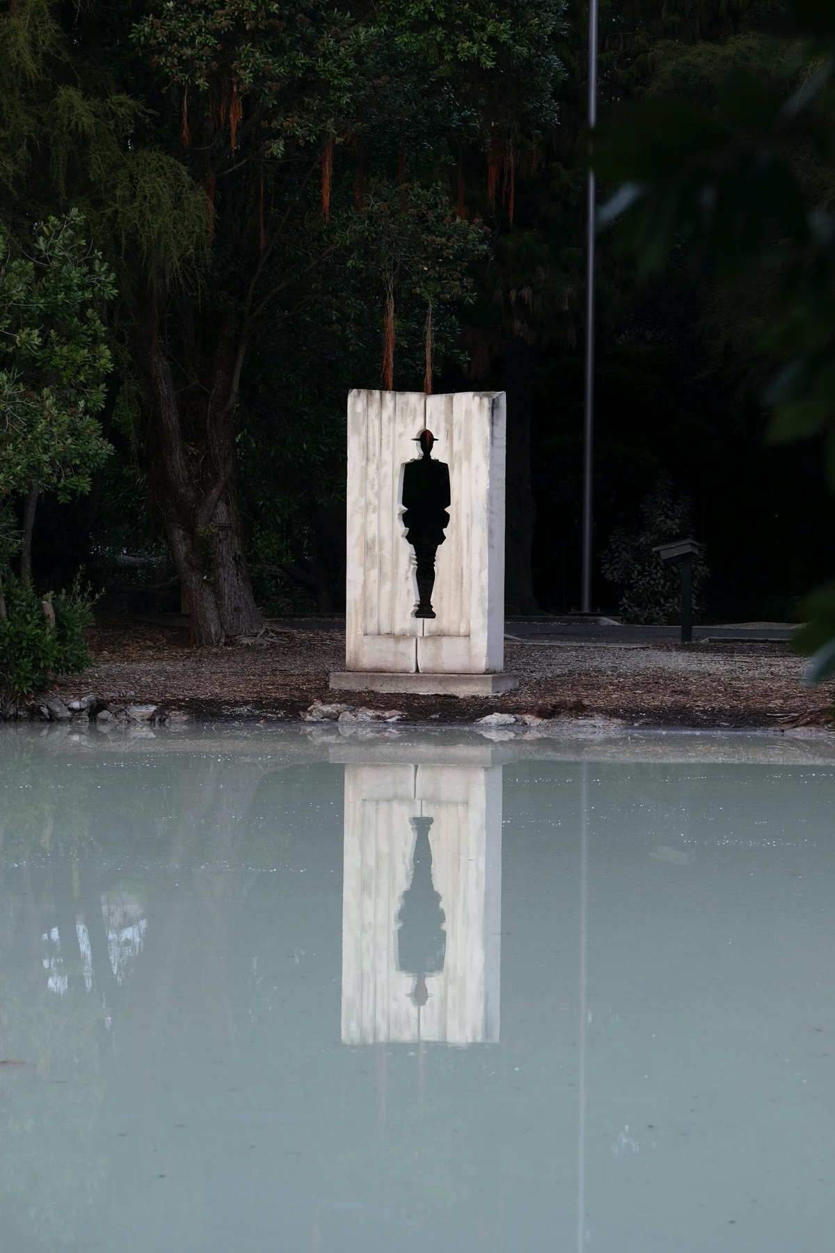 White lake, white stone slab with the black figure of a soldier cut out of it, reflected in the lake.