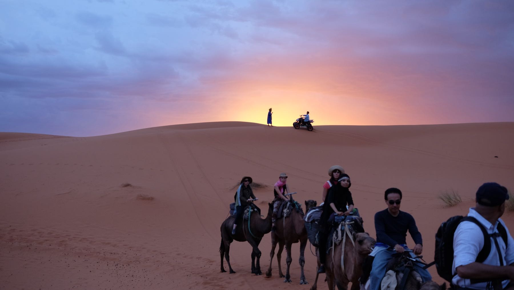 Sun rising over desert with locals silhouetted, rear end of camel train near the camera.
