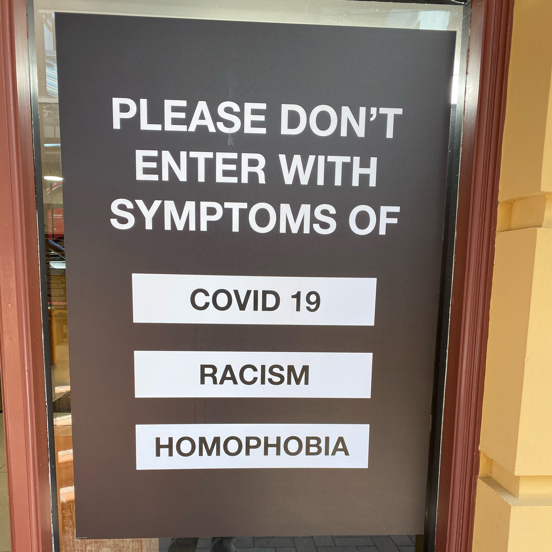 Shop window sign with words: please dont enter with symptoms if Covid 19, racism, homophobia.