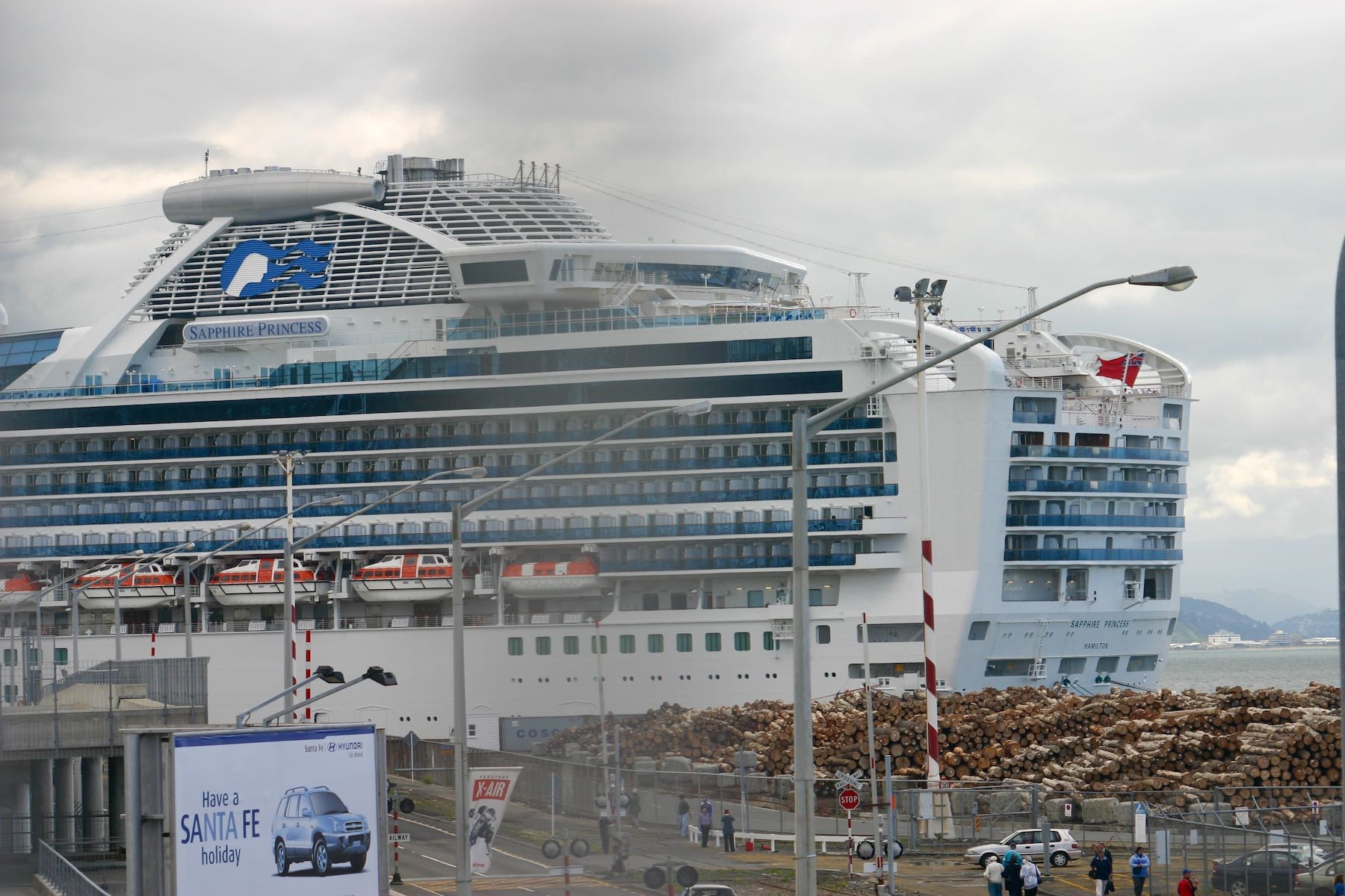 Sapphire Princess cruise ship with grids of cabin windows, next to a grid of logs waiting for export.