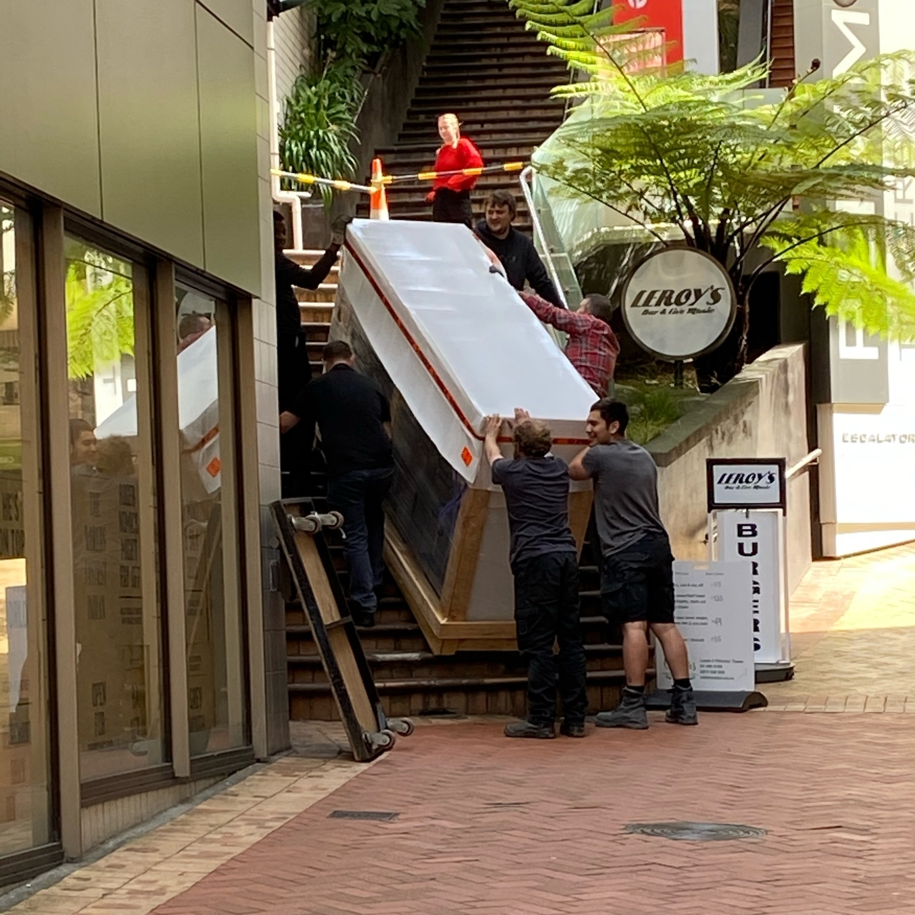 Six men moving a huge wrapped object up a set of steps.