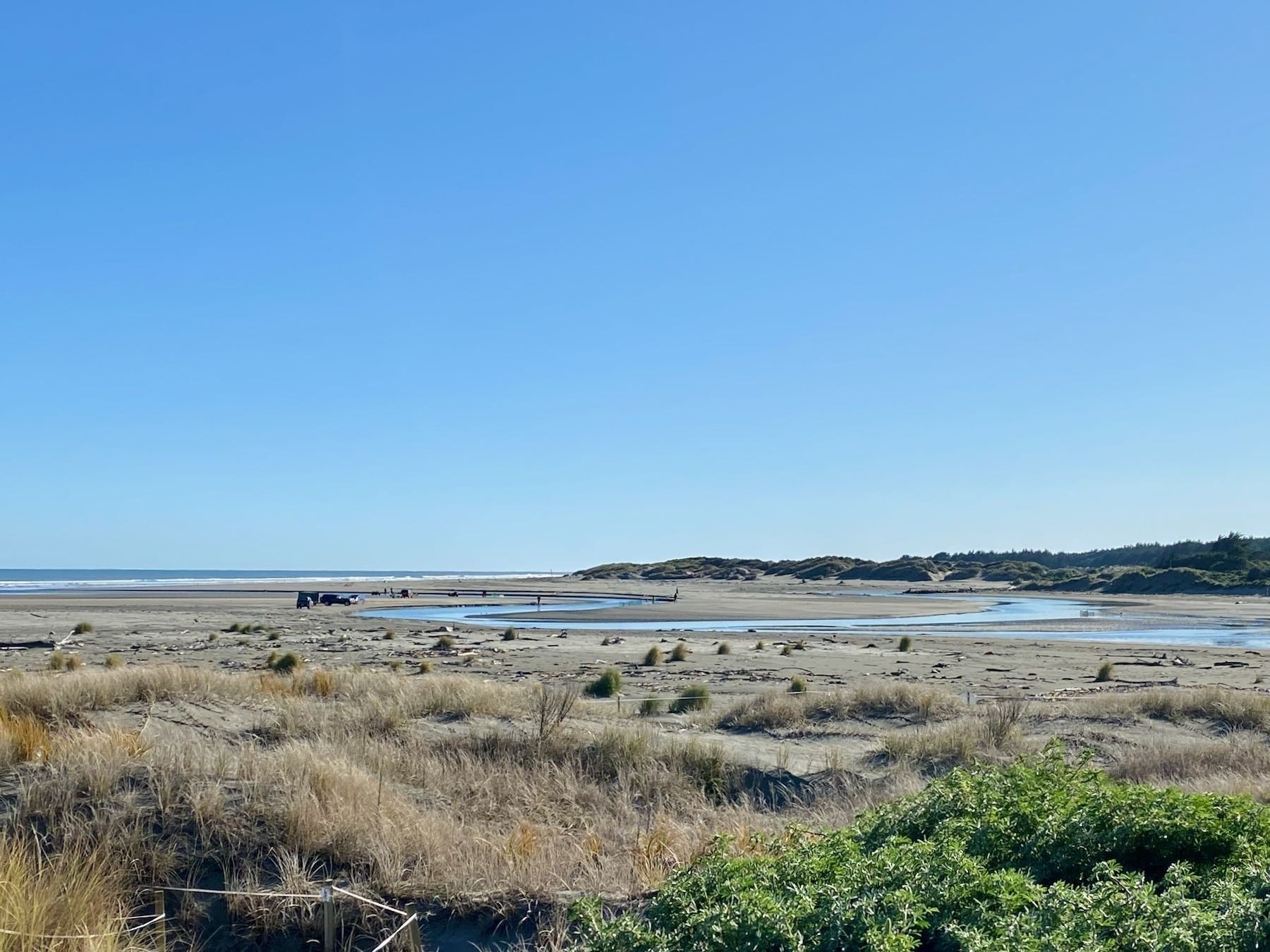 View across flat sand and dunes to the river mouth.