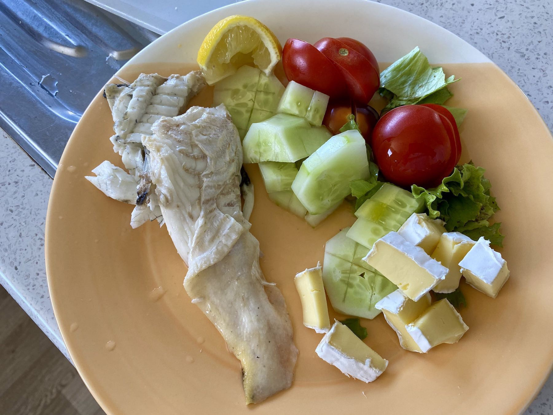 A meal of flounder, lettuce, tomato, cucumber, camembert.
