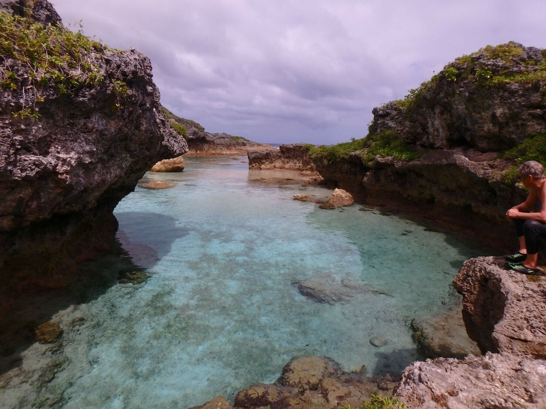 Green blue water, brown rocks and a violet sky.