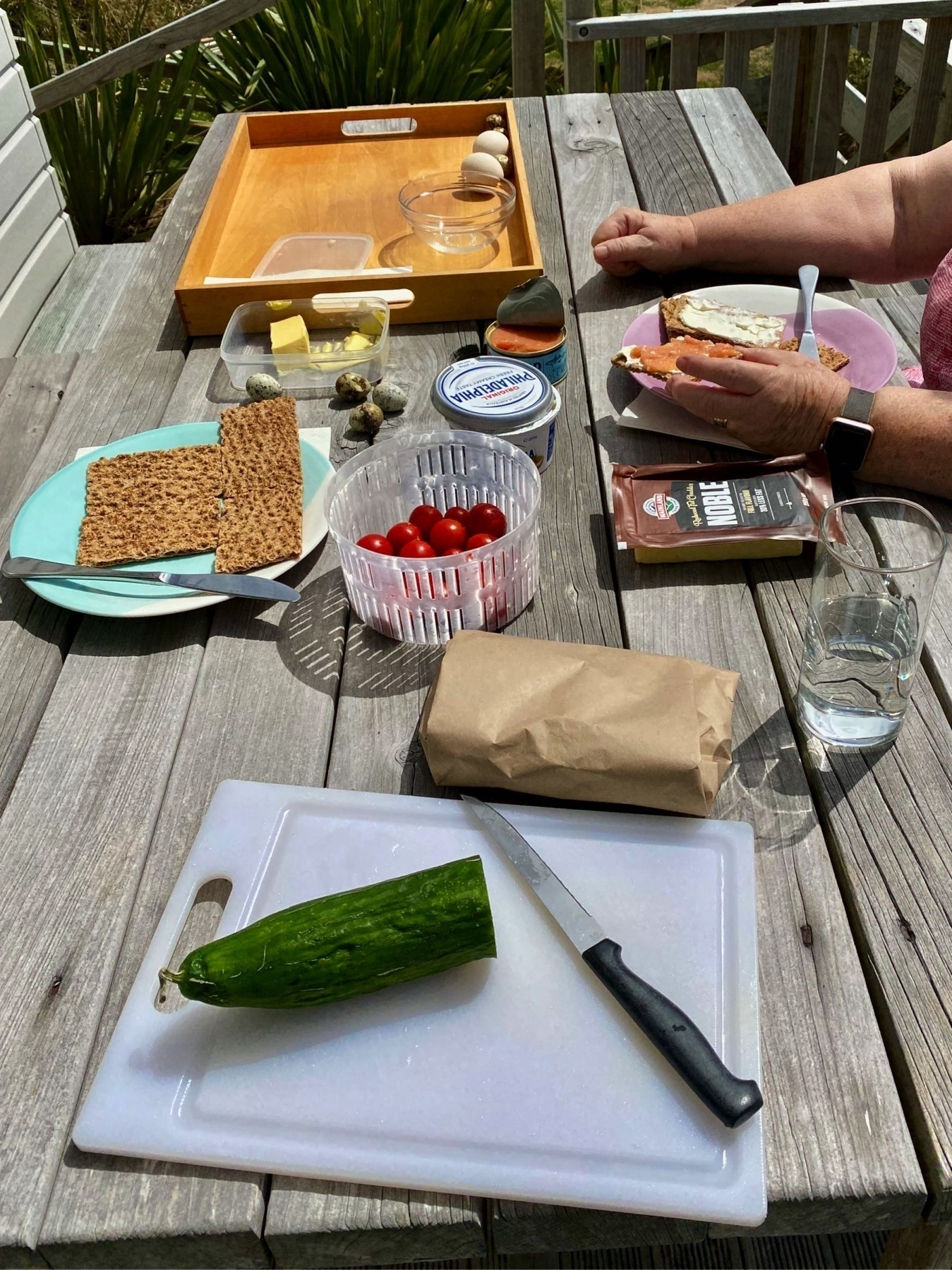 Picnic table in the sun with Swedish breakfast ingredients.