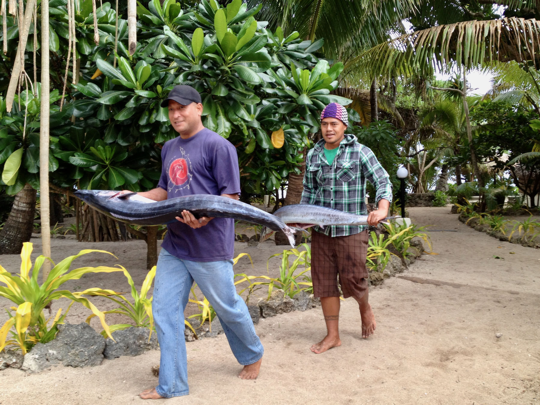 Two mean, each carrying a large fish.